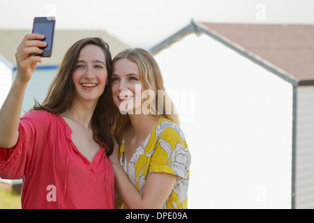 Two young female friends taking self portrait, Whitstable, Kent, UK - Stock Photo