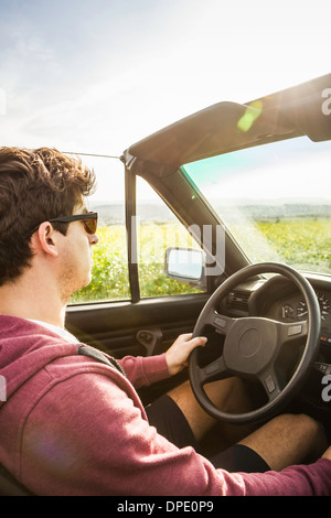 Young man leaning driving convertible - Stock Photo