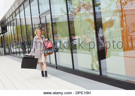 Mid adult female shopper walking on street with bags - Stock Photo