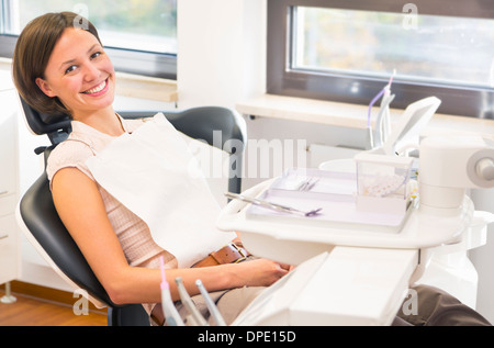Portrait of young woman in dentists chair, smiling - Stock Photo