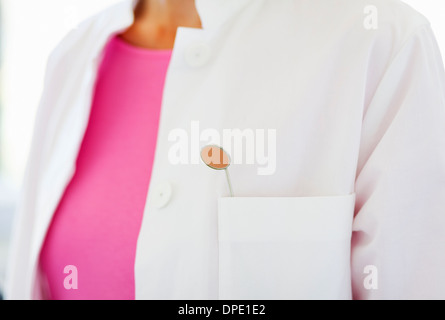 Close up of dental mirror in dentists pocket - Stock Photo