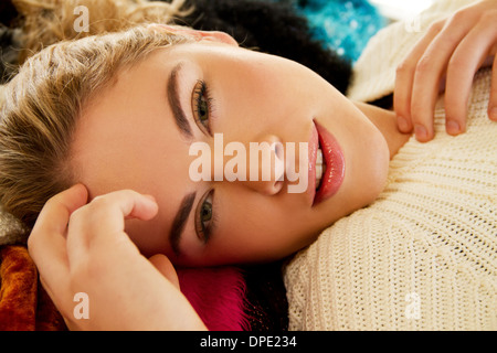 Close up portrait of young woman lying on furry blanket - Stock Photo