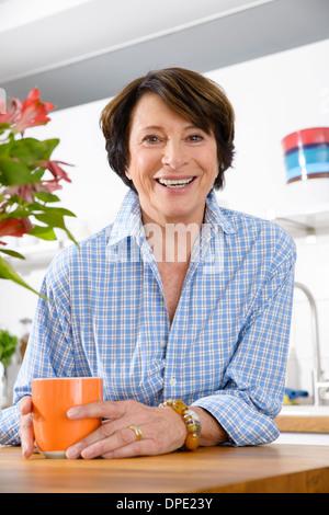 Portrait of youthful senior woman in kitchen - Stock Photo