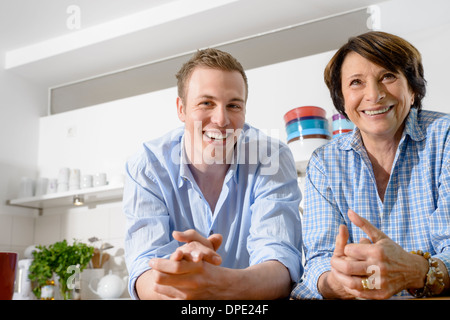 Portrait of youthful grandmother with grandson in kitchen - Stock Photo
