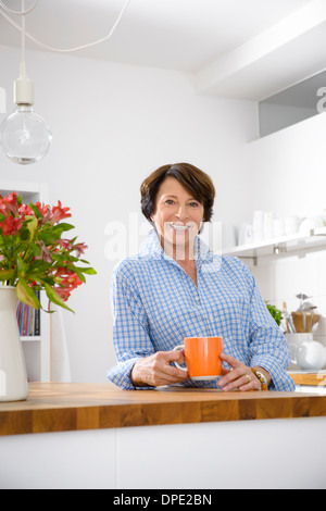Portrait of youthful senior woman at home in kitchen - Stock Photo