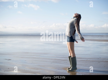 Young woman standing on beach looking up, Brean Sands, Somerset, England - Stock Photo