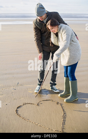 Young couple drawing heart in sand, Brean Sands, Somerset, England - Stock Photo