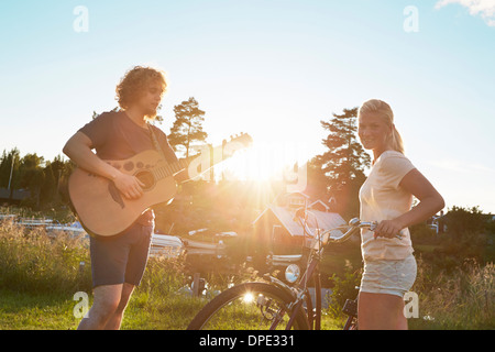 Young couple enjoying guitar, Gavle, Sweden - Stock Photo
