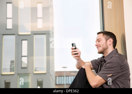 Businessman sitting on windowsill using smartphone - Stock Photo