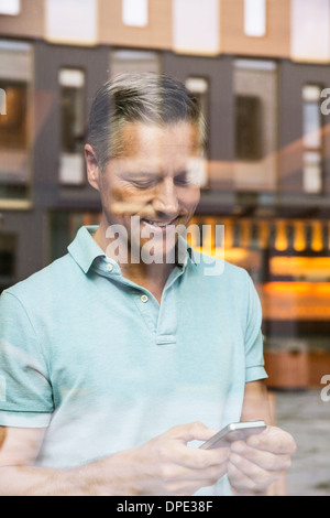 Businessmen making phone call, view through window - Stock Photo