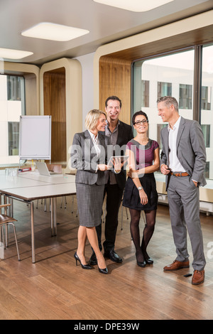 Businesspeople standing in conference room - Stock Photo