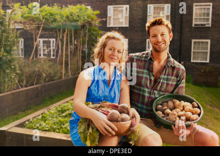 Couple with harvested potatoes and beets on council estate allotment - Stock Photo