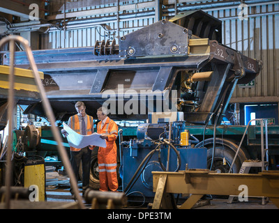 Engineers inspecting engineering drawings together in factory - Stock Photo