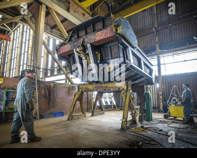 Engineers working on steel part in factory - Stock Photo