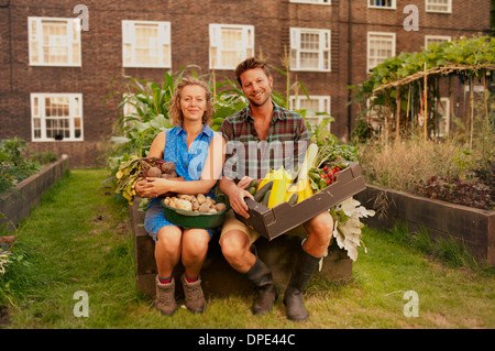Couple holding harvested vegetables on council estate allotment - Stock Photo
