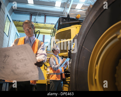 Engineers with engineering drawings inspecting heavy truck - Stock Photo