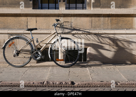 A bicycle leans against an old college wall in Cambridge UK. THe city is known as cycle city. - Stock Photo