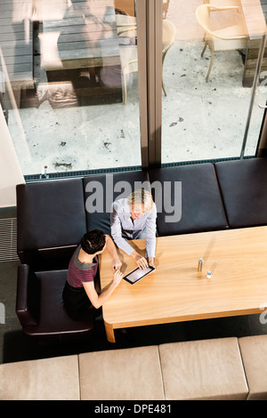 Elevated view of businesswomen using digital tablet - Stock Photo
