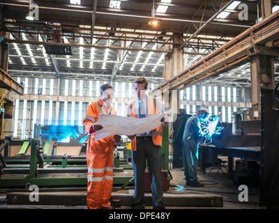 Engineers inspecting engineering drawings in factory - Stock Photo