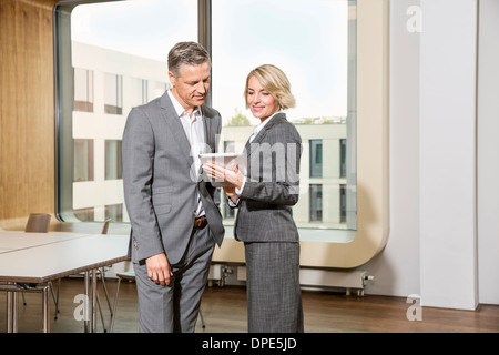 Businesspeople standing in conference room, using digital tablet - Stock Photo
