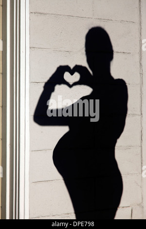 Silhouette of a pregnant woman in the background wall - Stock Photo
