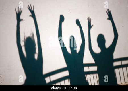 Creative photo of ecstatic people shadows on white wall - Stock Photo