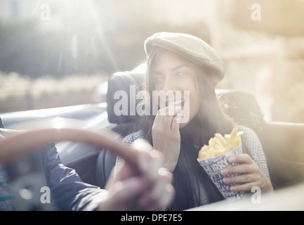 Young couple in convertible, woman eating chips - Stock Photo