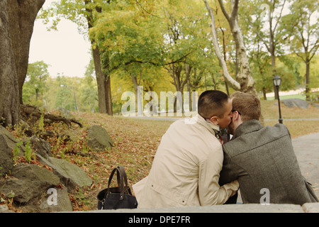 Man kissing partner on cheek in park - Stock Photo