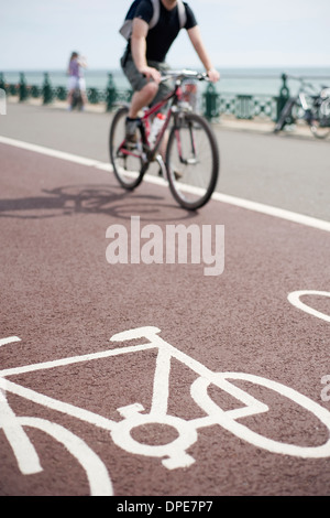 Cyclist cycling along a designated cycle path on Brighton Seafront, Sussex, England - Stock Photo