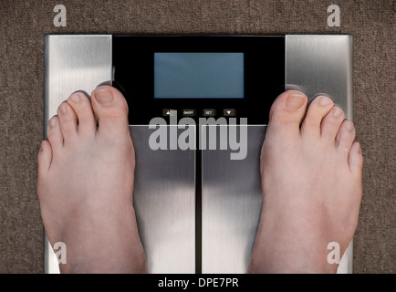 Man's Feet on Bathroom Scales on Carpet photographed from above with a Blank Display - Stock Photo