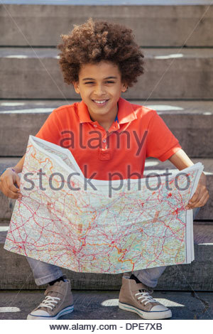 Portrait of boy sitting on steps with map - Stock Photo
