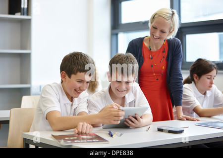 Schoolchildren working in class with teacher - Stock Photo