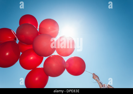 Hands holding bunch of red balloons against blue sky - Stock Photo