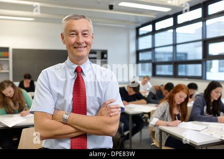 Portrait of mature male teacher in classroom - Stock Photo
