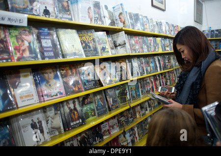 A lady buys pirated movie DVDs in a store in Sanlitun, Beijing, China. 11-Jan-2014 - Stock Photo