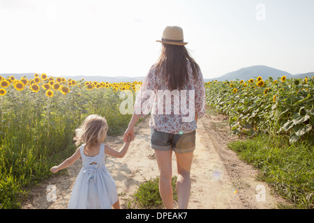 Mother and daughter walking through field of sunflowers - Stock Photo