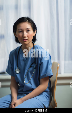 Portrait of a young female doctor sitting in office - Stock Photo
