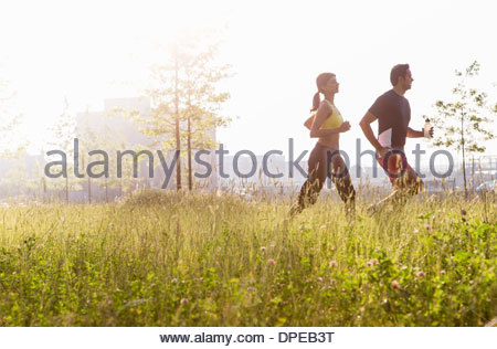 Couple jogging in park - Stock Photo