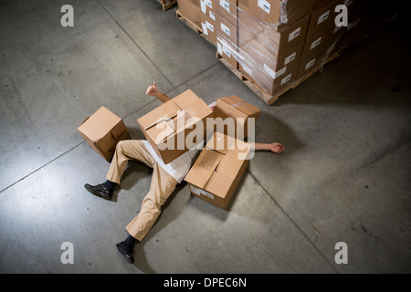 Man lying on floor covered by cardboard boxes in warehouse - Stock Photo