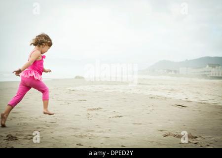 Female toddler running on beach - Stock Photo