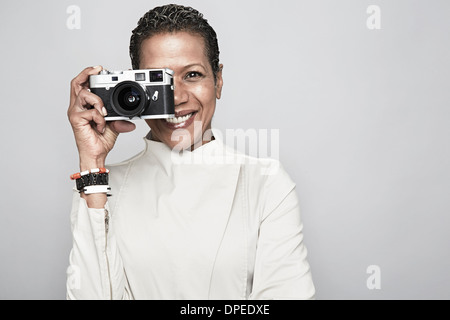 Studio portrait of happy mature woman holding up camera - Stock Photo