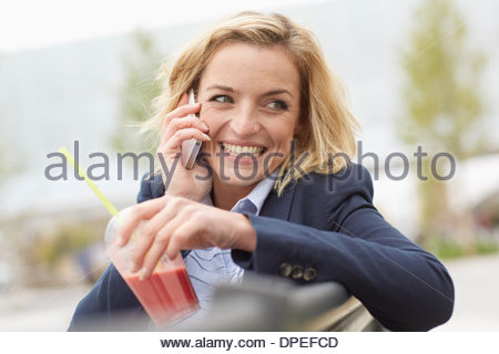 Office worker having lunch break on park bench - Stock Photo