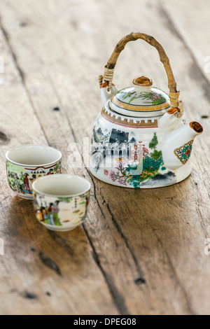 Chinese porcelain teapot and two cups on a wooden table - Stock Photo