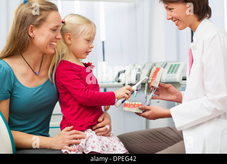 Dentist teaching girl on mothers lap how to brush teeth - Stock Photo