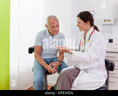 Female doctor talking to senior male patient - Stock Photo