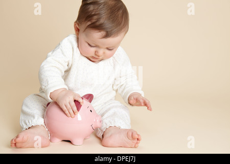 Studio portrait of baby girl playing with piggy bank - Stock Photo