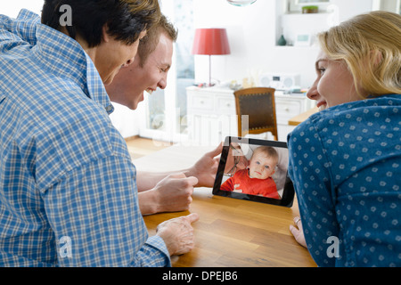Grandmother and adult grandchildren looking at photo of baby boy on digital tablet - Stock Photo