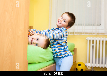 Two happy children playing at home - Stock Photo