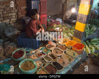 Young man selling spices at a street market in New Delhi at night, India - Stock Photo