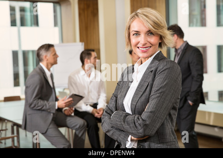 Businesswoman standing in front of colleagues - Stock Photo